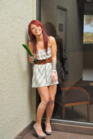 Naughty redhead Madelyn hikes up her skirt to fuck a large cucumber