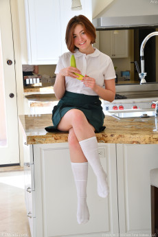 Gorgeous redhead schoolgirl teen Aria gives some upskirt shots before sticking a banana in her trimmed pussy