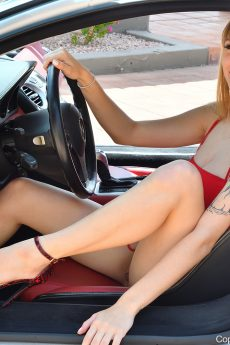 Blonde bombshell Angel hikes up her dress and shows her ass, pussy and heavy hangers by a car
